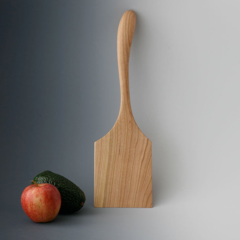 Cherry wood griddle spatula with rectangular blade and curved handle.