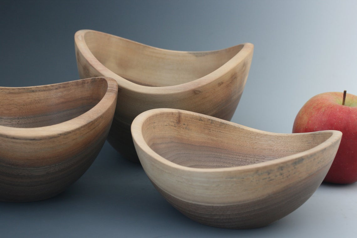 Examples of walnut live edge bowls with a sanded smooth freeform edge.